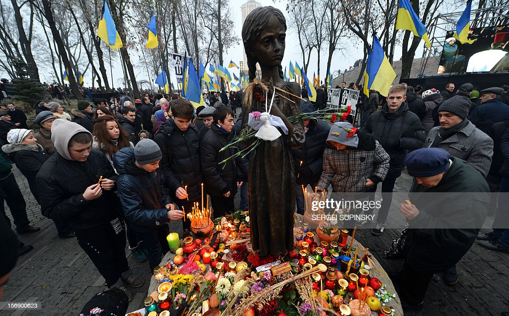 People set up candles around a statue in memory of the victims of the Holodomor famine during a ceremony at the Holodomor memorial in Kiev on November 24, 2012. Ukraine marked 80 years since the Stalin-era Holodomor famine, one of the darkest pages in its entire history that left millions dead and which is regarded by many as a genocide. The 1932-33 famine took place as harvests dwindled and Josef Stalin's Soviet police enforced the brutal policy of collectivising agriculture by requisitioning grain and other foodstuffs.