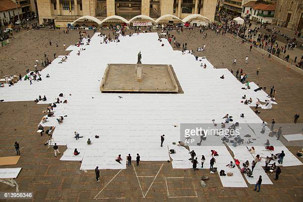 TOPSHOT People sew white cloths with names of victims of the Colombian conflict painted in ash at the Bolivar square in Bogota on October 11 2016...