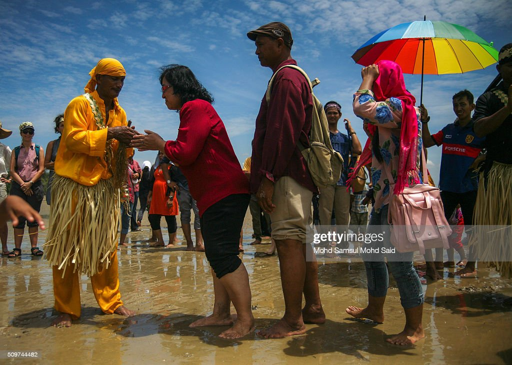 People shake hands with a shaman after performing a ritual prayer (Puja Pantai), which is a thanksgiving ritual to appease the spirits of the seas at Pulau Carey, Straits of Malacca beach on February 12, 2016 in Pulau Carey, Malaysia. Every year, the indigenous people of Mah Meri village, located in Pulau Carey, about 140 km (87 miles) southwest of Kuala Lumpur, perform the 'Puja Pantai' ritual prayer and 'Main Jo-oh' dance to appease the spirits of the seas and celebrate the New Year.