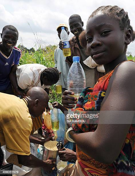 People share food aid at a food distribution set up by the UN World Food Programme near a camp for internally displaced persons in Bangui on December...