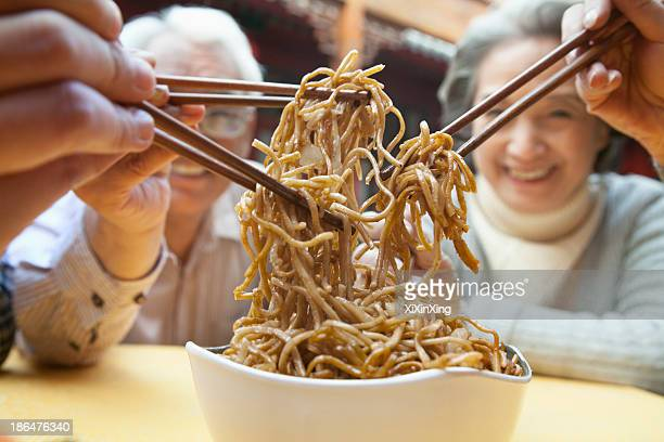 People sharing noodles, close-up