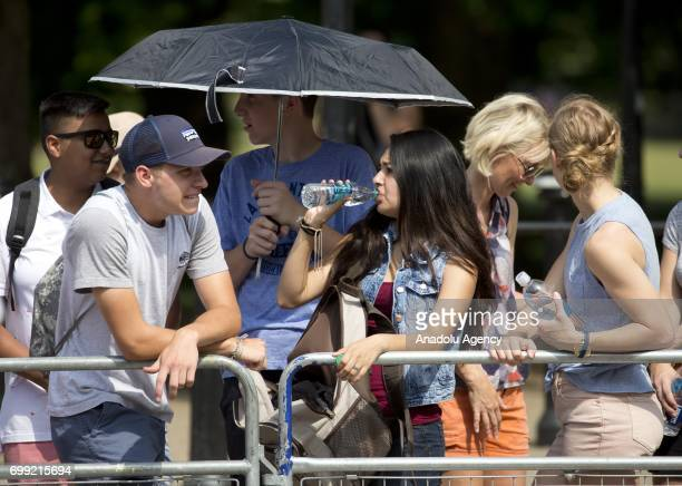 People shelter from the heat outside Buckingham Palace as they wait for the departure of Britain's Queen Elizabeth II to the Houses of Parliament to...