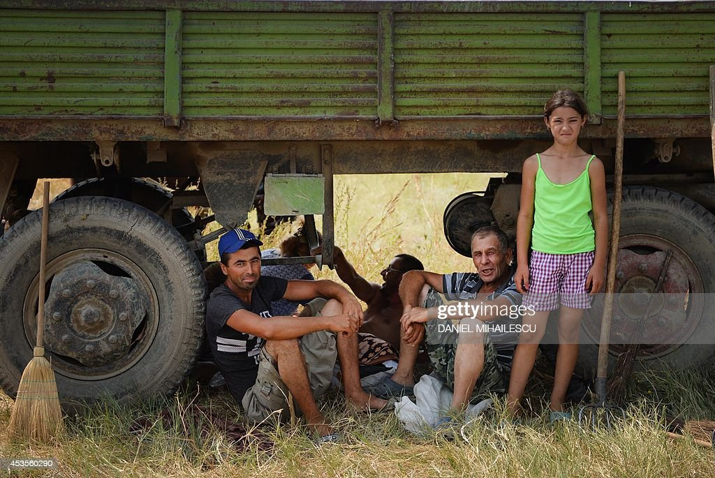 People shelter from the heat under a car in a field next to Garliciu village on August 13, 2014. Forecasters have issued an alert announcing temperatures of up to 38 degrees Celsius.