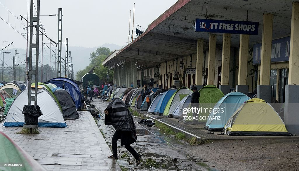 People shelter from the rain at a makeshift camp for migrants and refugees near the village of Idomeni not far from the Greek-Macedonian border on April 29, 2016. Some 54,000 people, many of them fleeing the war in Syria, have been stranded on Greek territory since the closure of the migrant route through the Balkans in February. / AFP / TOBIAS