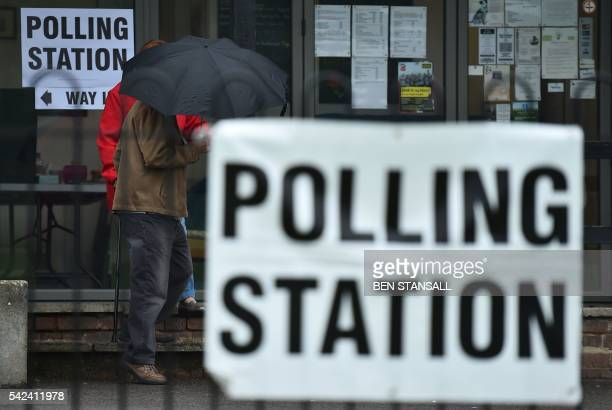 People shelter from the rain beneath an umbrella as they leave a polling station set up inside a sports club cafe in Croydon south of London on June...