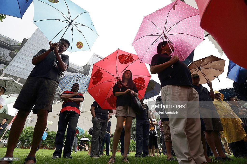 People shelter from the rain under umbrellas in Hong Lim Park to protest against the government's White Paper on Population at Speakers' Corner on February 16, 2013 in Singapore. Thousands of protesters gathered today following the release of a government white paper on population that revealed it could increase 30% to 6.9 million by 2030, angering residents who already see a strain on housing, transportation and healthcare.