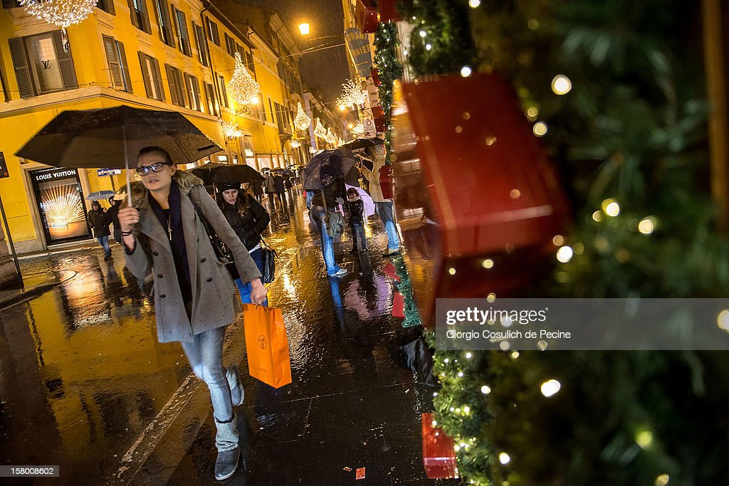 People shelter from the rain with umbrella as they walk through the streets decorated with Christmas lights in downtown area on December 8, 2012 in Rome, Italy.