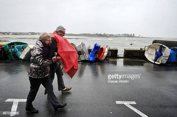 People shelter from the wind in Ploemeur western France as Brittany and the Atlantic coasts wait for the storm named Qumaira on February 6 2014 The...