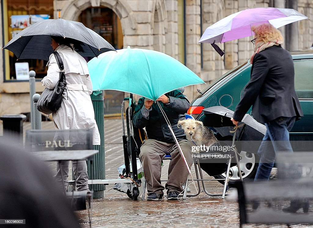 People shelter themselves from the rain on September 11, 2013, in Lille.