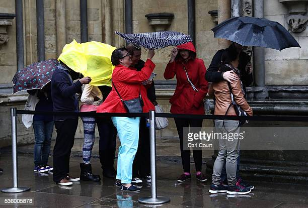 People shelter under a plastic sheet and umbrellas as they queue in heavy rain to enter Westminster Abbey on May 31 2016 in London England Heavy rain...