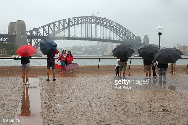 People shelter under umbrellas from the rain and pose for pictures in front of the Sydney Harbour Bridge on January 5 2016 in Sydney Australia Sydney...
