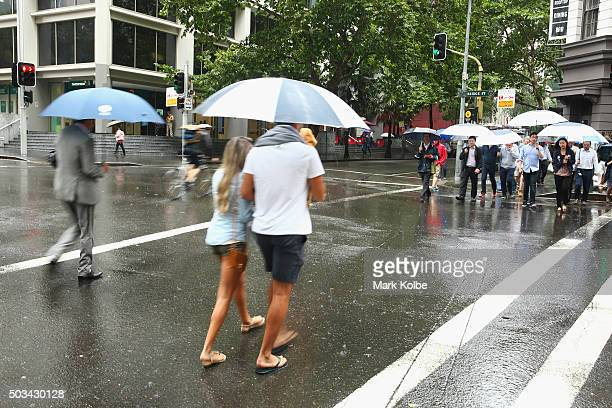 People shelter under umbrellas from the rain as they cross the street in the Sydney central business district on January 5 2016 in Sydney Australia...