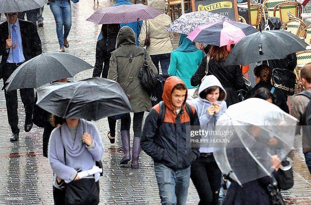 People shelters themselves from the rain as they walk down a street on September 11, 2013, in Lille.