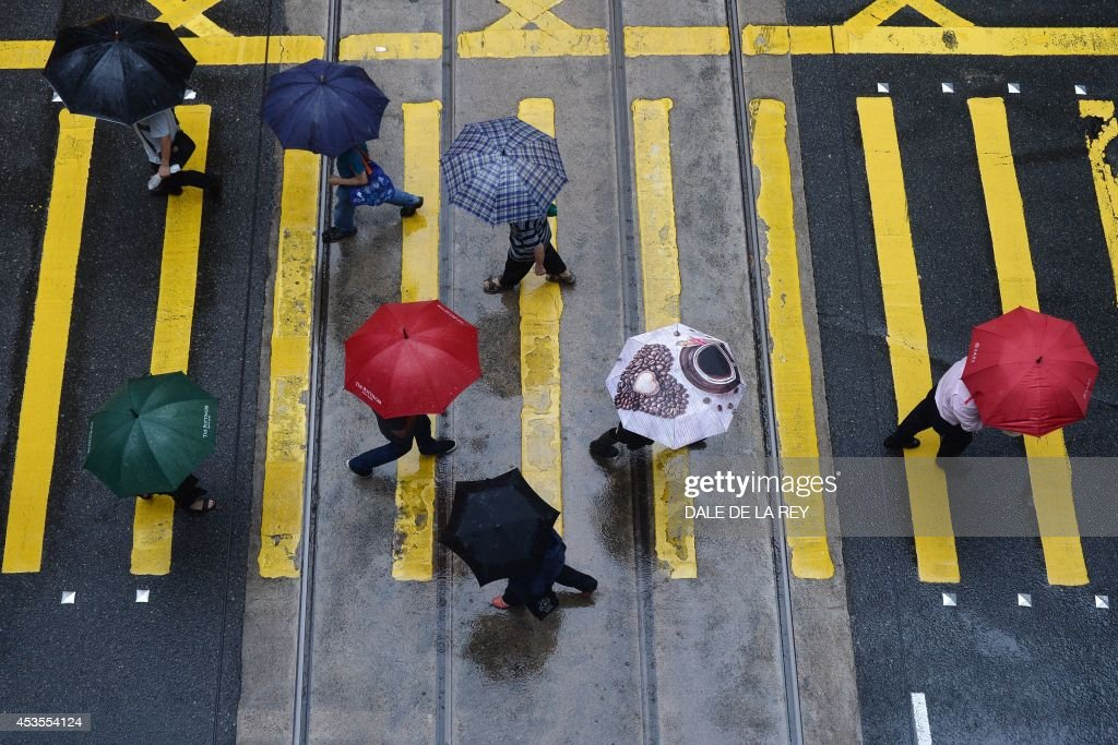 People shield themselves from the rain with umbrellas as they cross an intersection in Hong Kong on August 13, 2014. An active southwesterly airstream associated with a trough of low pressure is bringing thundery showers to the south China coast, the Hong Kong weather observatory reported.