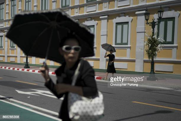 People shield themselves from the sun as they gather to pay their respects to Thailand's late King Bhumibol Adulyadej near the Royal Palace as the...