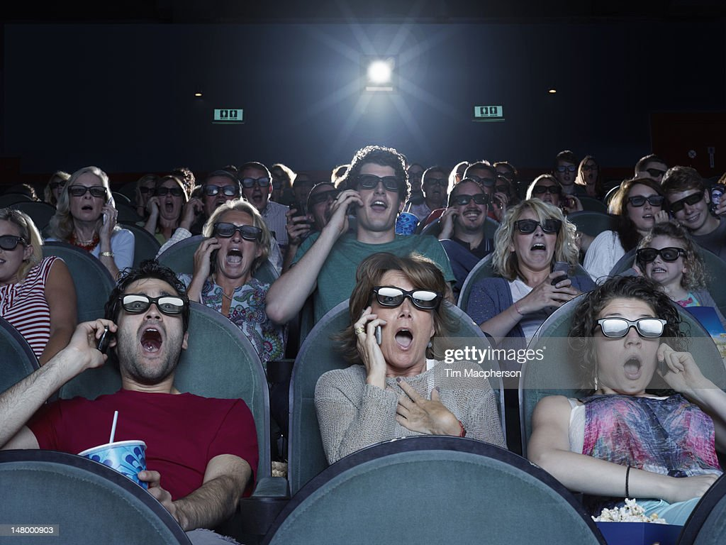 People shocked at a movie theater on their phones : Stock Photo
