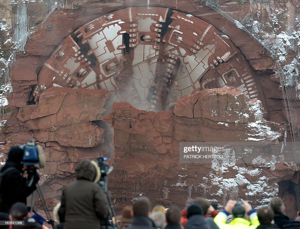 People shoot and take pictures of a giant drilling machine completing the 4 kilometre-long Saverne tunnel beneath the Vosges mountains in Eckartswiller, eastern France during a ceremony on February, 25, 2013, as part of the second phase of construction works for the east European high speed train line (LGV) between Paris and Strasbourg. The line is to bound in 2016 Paris and Strasbourg in 1h50 at a speed of 320 km per hour.