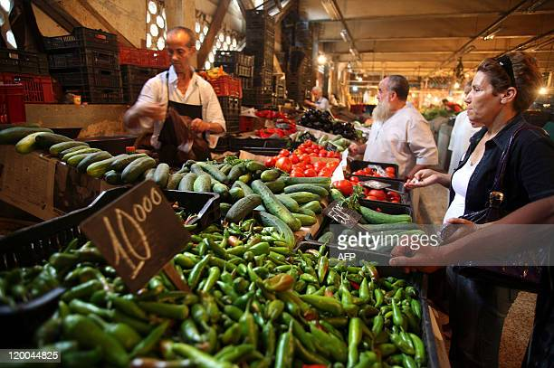 People shop a stand at Ali Mellah market in Algiers on July 27 2011 Faced with crumbling regimes across the Arab world Algeria has dramatically...