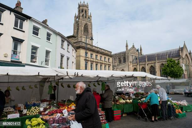 People shop at a fruit and vegetable stall in Boston Market on May 13 2017 in Boston United Kingdom The town of Boston in Lincolnshire voted with a...