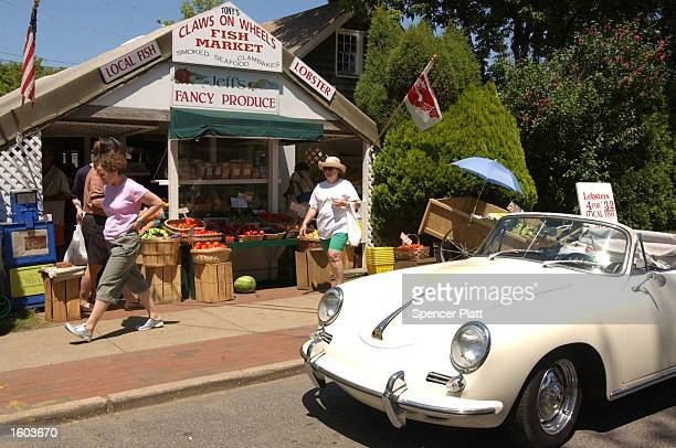 People shop at a fruit stand July 22 2001 in Easthampton NY The Hamptons located at the east end of New York''s Long Island is a traditional summer...