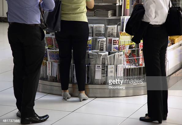 People shop at a kiosk as newspapers including the Nikkei center are displayed for sale in Tokyo Japan on Friday July 24 2015 After almost six...