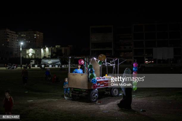 People shop at a street vendors stall in park on July 19 2017 in Gaza City Gaza For the past ten years Gaza residents have lived with constant power...
