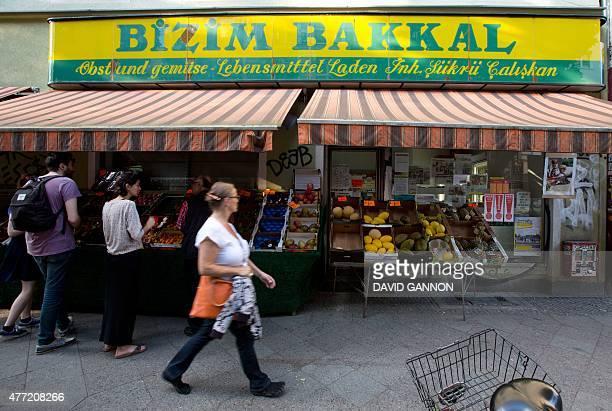 People shop at Ahmet Caliskan's fruit and vegetable shop Bizim Bakkal in the Wrangel Street in Berlin's Kreuzberg district on June 12 2015 Local...
