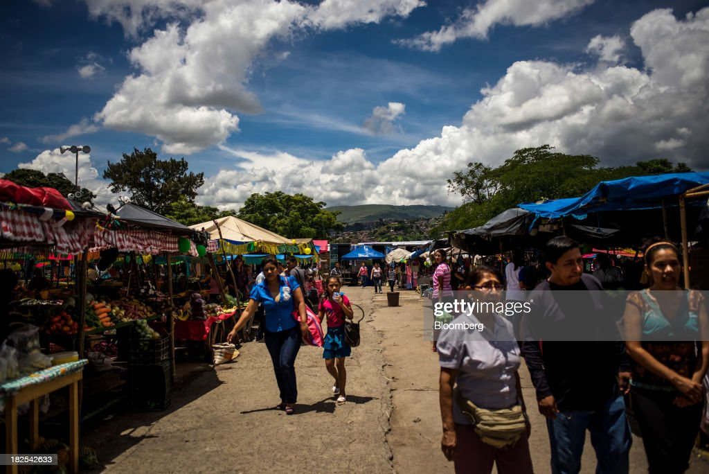 People shop at an openair market in Tegucigalpa Honduras on Saturday Sept 7 2013 Economic growth in Honduras is forecast to slow to 3 percent this...