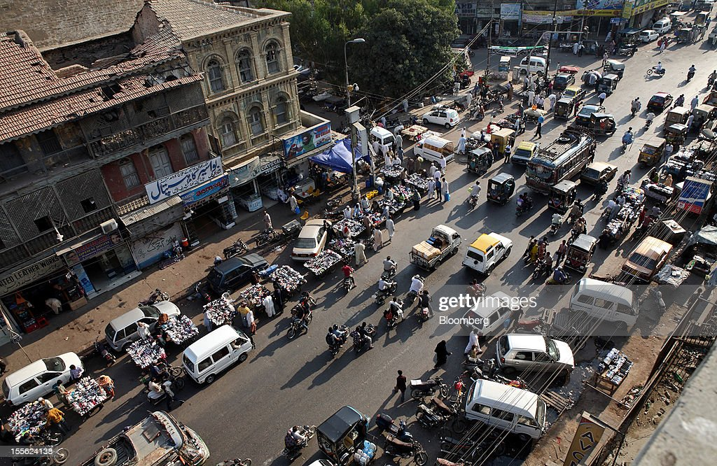 People shop at roadside stalls as traffic moves along M.A. Jinnah Road in Karachi, Pakistan, on Wednesday, Oct. 31, 2012. Businesses in Pakistan's commercial capital are bracing for a surge in extortion demands as parties representing the city's ethnic communities seek to use their hired guns to build financial war chests ahead of parliamentary polls due in the first half of next year. Photographer: Asim Hafeez/Bloomberg via Getty Images