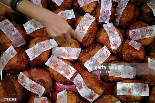 People shop for Christmas hams at a shop in the Quiapo district of Manila December 18 2010 Hams are a traditional Christmas treat in the Philippines...