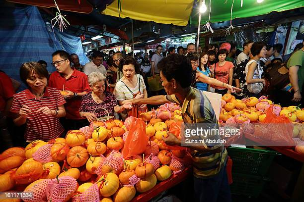 People shop for fruits on the final day of street sales in Chinatown on February 9 2013 in Singapore Thousands gathered today to celebrate the...