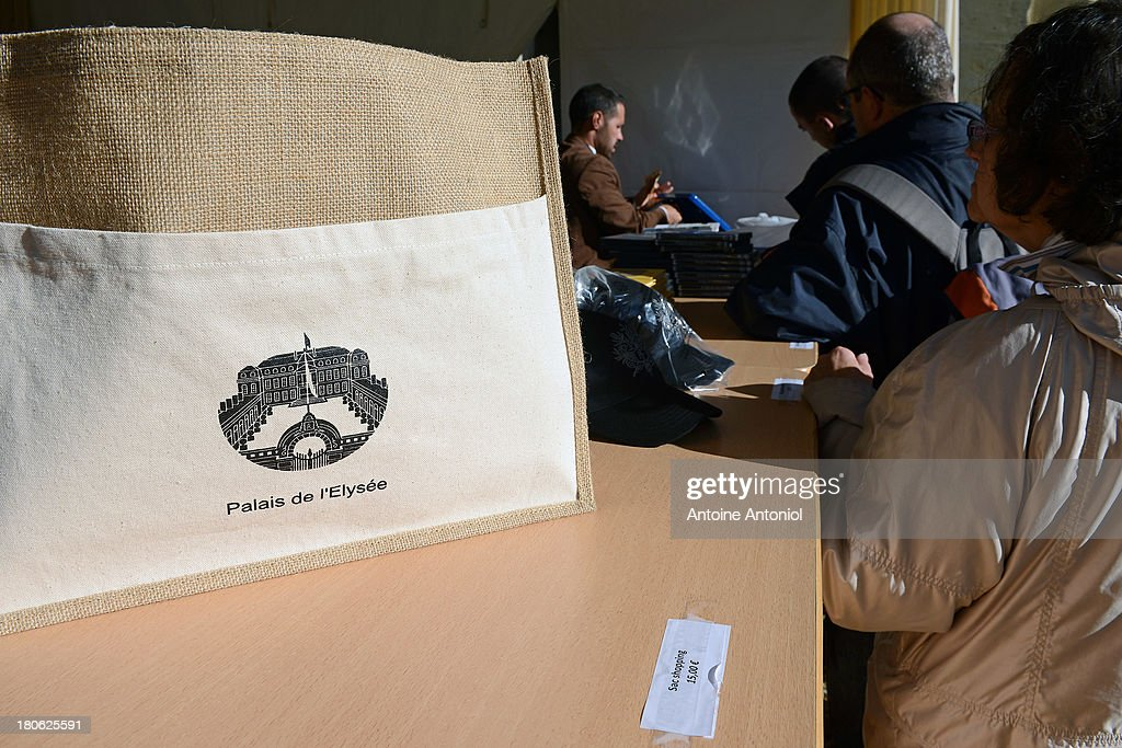 People shop for souvenirs at French President car at the Elysee Presidential Palace during the 30th edition of France's European heritage days on September 15, 2013 in Paris, France. Monuments and state buildings are opened for free for two days to the public.