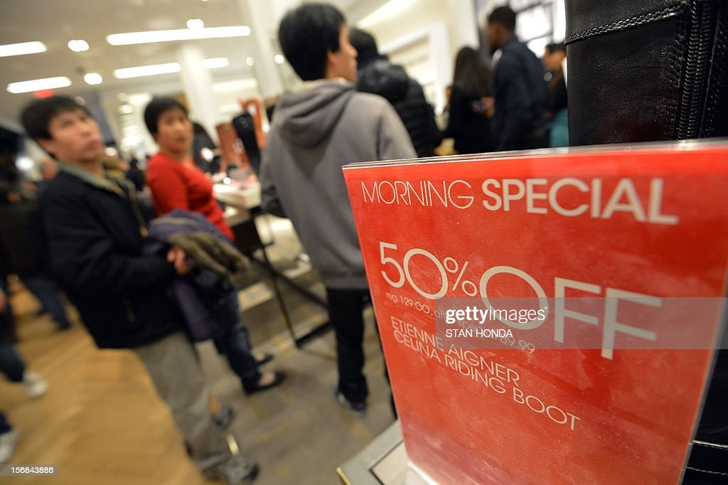 People shop in Macy's department store as they open at midnight (0500 GMT) on November 23, 2012 in New York to start the stores' 'Black Friday' shopping weekend. AFP PHOTO/Stan HONDA