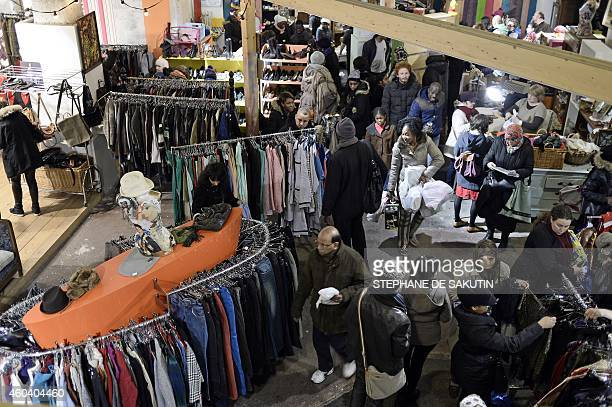 People shop on December 13 2014 during the 'Super Noel' sales of new and secondhand items of charity organization 'Emmaus Defi' in Paris on December...