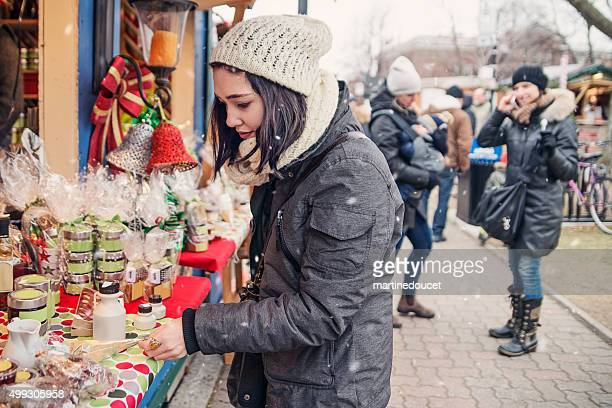 People shopping at an outdoors public market in winter.
