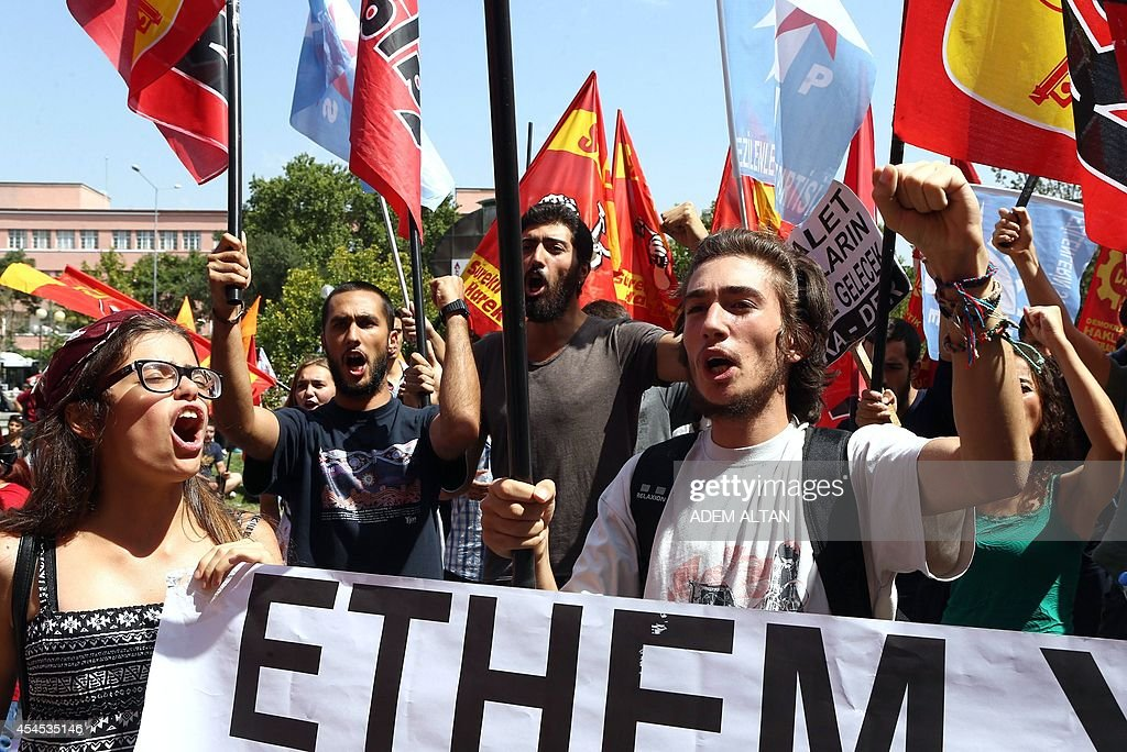 People shout and hold flags as they demonstrate outside the courthouse in Ankara on September 3, 2014, during the trial of a Turkish police officer accused of killing 26-year-old protester Ethem Sarisuluk in June 2013 during anti-government protests. Turkish police officer Ahmet Sahbaz was jailed for seven years and nine months on September 3 after being convicted of killing Sarisuluk during 2013 anti-government protests.