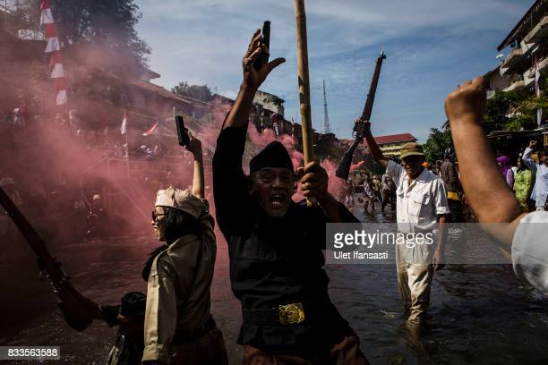 People shout as they perform a theatrical battle for independence during celebrations for the 72nd Indonesia National Independence day at Code river...