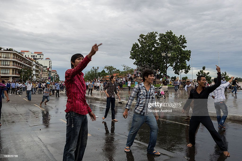 People shout at anti-riot police as clashes erupt near the riverside on September 15, 2013 in Phnom Penh, Cambodia. The CNRP plan a three day demonstration to contest the Cambodian national election results.