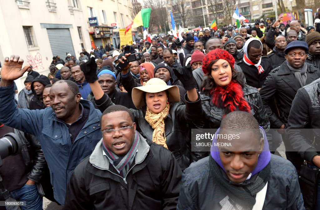 People shout during a demonstration, organized by Malian associations, in support of the liberation forces of Mali on January 26, 2013 in Montreuil, near Paris. Placard reads 'For a united Mali, against terrorism'.