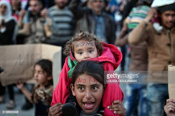 TOPSHOT People shout 'No Turkey' at the port of the town of Chios where refugees and migrants who broke out from the Vial detention center camp out...