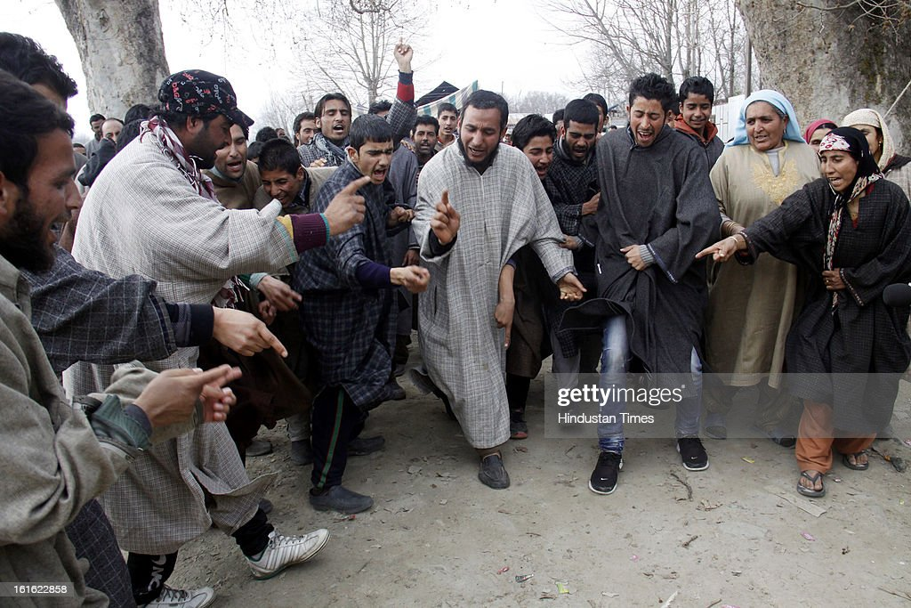 People shout slogan outside the house of Afzal Guru after curfew was lifted in some areas on February 13, 2013 in Sopore some 50 Km from Srinagar, India. Curfew was was imposed by the authorities last Saturday to control Law and order situation after the execution of Parliament attack convict Afzal Guru.