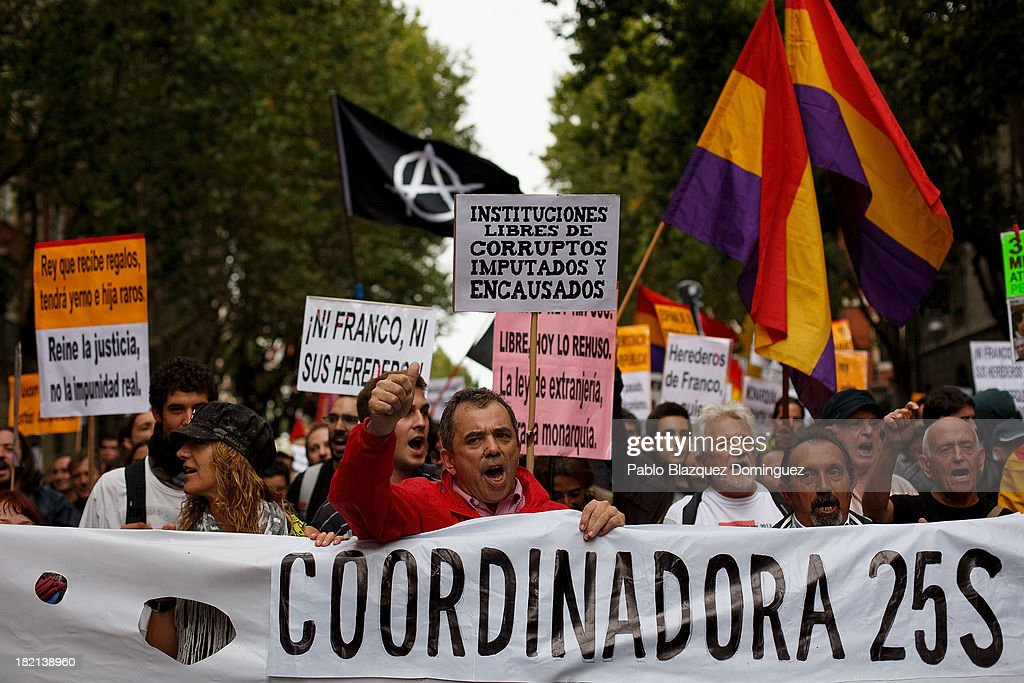 People shout slogans and hold placards during a demonstration against the Spanish Monarchy under the header 'Check the King' at Princesa Street on September 28, 2013 in Madrid, Spain. Organizers call for a demonstration on the anniversary of 'Surround the congress protest' to claim the abolition of the Monarchy. Currently King Juan Carlos of Spain is in hospital recovering from a hip operation. The Spanish Royal Family has lost popularity since the King injured his hip on elephant hunting trip and the King's son-in-law, Inaki Urdangarin is being investigated over a corruption scandal.