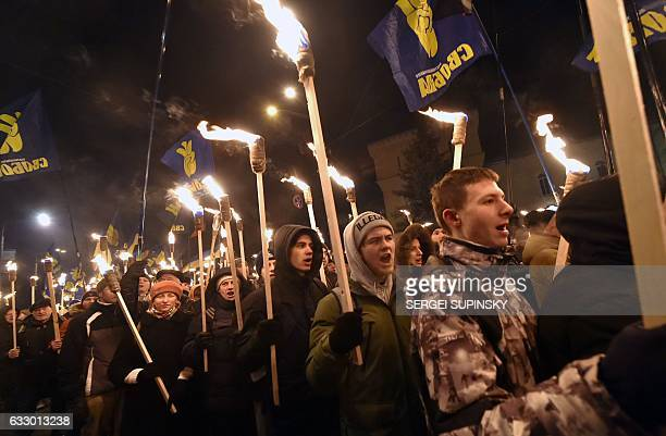People shout slogans as they carry torches during a fewthousand march organized by Svoboda Ukrainian nationalist party in Kiev on January 29 to mark...