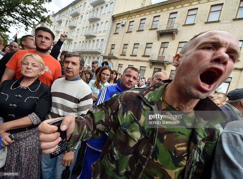 People shout slogans during a rally in front of Ukrainian President Petro Poroshenko's office in Kiev on August 27, 2014. Protesters demand help for the volunteer battalions of Donbass, Mirotvorets, Kherson and Dnipro-1 surrounded by pro-Russian militants for the fifth day in the small city of Izvaryne, suburb of the eastern Ukrainian city of Donetsk.
