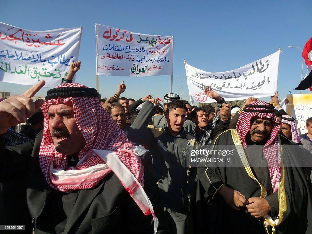 People shout slogans holding placards during a demonstration on January 4, 2013 in the northern Iraq's Kirkuk province as part of a national day of rallies by Sunni Muslims criticising Iraq's premier and demanding the release of prisoners they say are wrongfully held.Thousands of Sunni Muslims demonstrated also in Baghdad, in the latest of nearly two weeks of rallies.