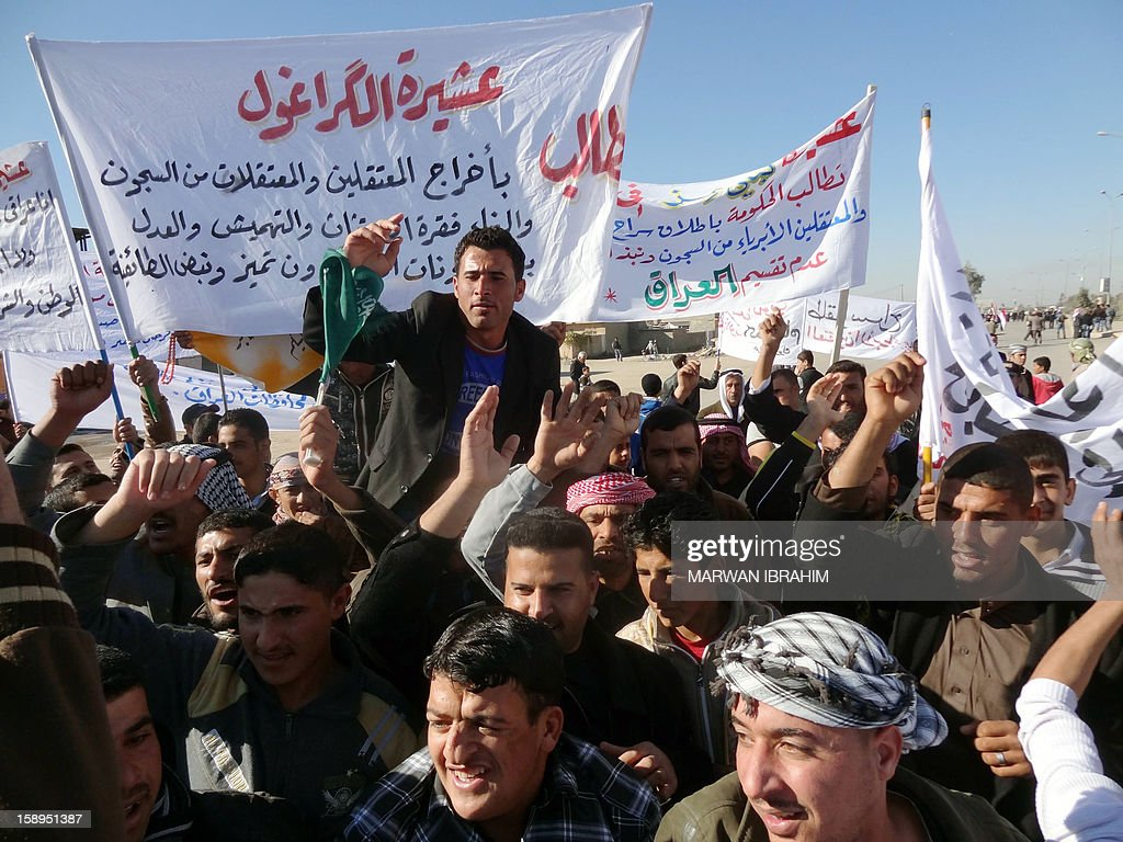 People shout slogans holding placards during a demonstration on January 4, 2013 in the northern Iraq's Kirkuk province as part of a national day of rallies by Sunni Muslims criticising Iraq's premier and demanding the release of prisoners they say are wrongfully held.Thousands of Sunni Muslims demonstrated also in Baghdad, in the latest of nearly two weeks of rallies. AFP PHOTO MARWAN IBRAHIM