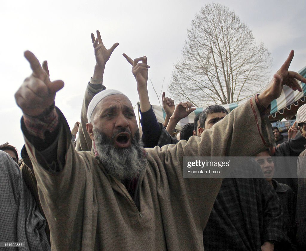 People shout slogans outside the house of Afzal Guru after curfew was lifted in some areas on February 13, 2013 in Sopore some 50 Km from Srinagar, India. Curfew was was imposed by the authorities last Saturday to control Law and order situation after the execution of Parliament attack convict Afzal Guru.