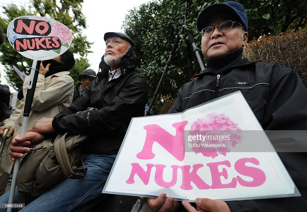 People show placards during a rally denoucing nuclear power plants in front of the Diet building in Tokyo on November 11, 2012. Several thousand people took part in the rally. AFP PHOTO/Toru YAMANAKA