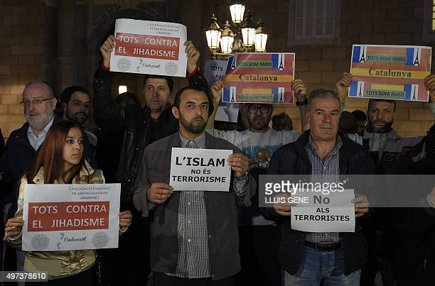 People show posters reading 'Islam is not terrorism' and 'all against jihadism' during a demonstration called by the IBN Battuta Foundation on behalf...