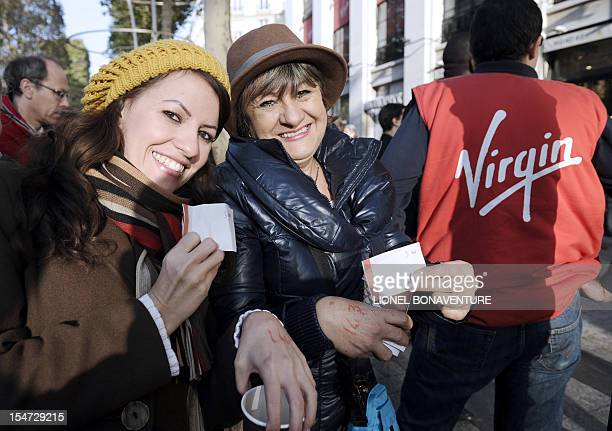 People show receipts after buying tickets at the Virgin megastore in Paris on October 25 2012 for a concert held the same day in the French capital...